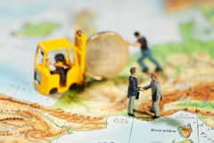 Reaching Accord On European Debt. Twpo miniature figurines of businessmen shaking hands while a Euro coin is loaded on to a forklift, map of Europe, concept Royalty Free Stock Photography