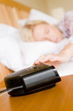 Reaching For Alarm. A young attractive woman in bed reaching for snooze button Stock Images