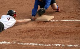 Reaching for the Base. A player who slid past the base and is reaching back to touch it Royalty Free Stock Photo