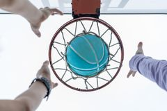 Reaching for a basketball in the net stock photo