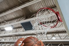 Reaching for basketball under hoop Royalty Free Stock Images