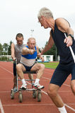 Reaching For The Baton. Disabled person and his helper reaching for an other athlete to pass him the baton. Caricature picture to illustrate helping, giving royalty free stock photography