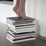 Reaching a book in the library stock images