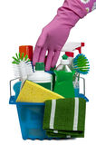 Reaching For Cleaning Products. Pink gloved hand reaching for cleaning products in a blue basket. Isolated on white with small shadow under green rag stock photo