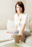 Reaching for coffee. Young woman reaching for a coffee mug Royalty Free Stock Photos