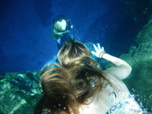 Reaching For The Deep. An underwater photograph of a girl swimming with an outstretched hand.  Another swimmer appears deeper inside the cavern.  The sunlight Stock Image