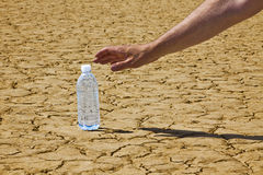 Reaching For Desert Bottled Water. A man's hand and arm is reaching in from the upper right corner down to a bottle of water sitting on a desert playa Royalty Free Stock Photography