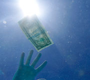Reaching dollar bill underwater Stock Photo