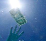Reaching dollar bill underwater. Against sun Stock Photo