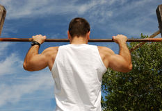 Reaching Goal. Strong Man Doing Pull-ups on a Bar in a Park Royalty Free Stock Image