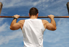 Reaching Goal. Strong Man Doing Pull-ups on a Bar in a Park Stock Images