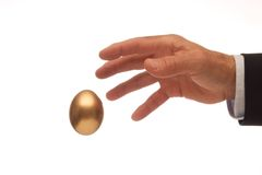 Reaching for the Golden Egg. Man's Hand Reaching for the Golden Egg Stock Photo