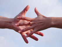 Reaching hands. Over the cloudy sky background Royalty Free Stock Photo