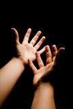 Reaching hands. Hands in outer space reaching into the darkness Royalty Free Stock Photography