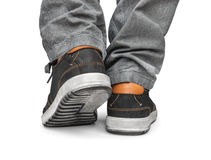Reaching leg men in gray jeans and street shoes Stock Photos