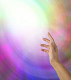 Reaching into the Light. Open hand reaching up towards a ball of white light on a multicolored background stock photo