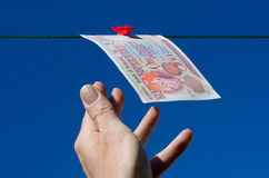 Reaching for one hundred pound note Stock Photos