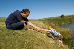 Reaching out. Father reaching out to his little child to help him climb up a steep wall Royalty Free Stock Images