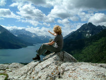Reaching out. Woman sitting on top of mountain Stock Photography