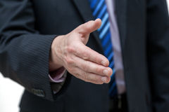 Reaching out a hand. A closeup of a man reaching out his hand in greeting Stock Photo
