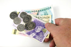 Reaching over swedish money Royalty Free Stock Images