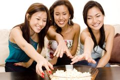Reaching For Popcorn. Three attractive asian women reach for popcorn Royalty Free Stock Images