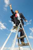 Reaching for the sky. A businessman on a ladder reaching for the sky as if the limit is beyond the sky Stock Photography