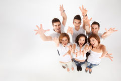 Reaching for the sky. Team of friends looking above, reaching for the camera royalty free stock photo