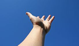 Reaching for the sky. Hand reaching for the sky- conceptual image Stock Image