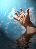 Reaching for sky. Male hand reaching for sky with simulated water reflection royalty free stock image