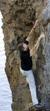 Reaching for something to hold on to. A handsome middle aged man climbs a rock face unprotected while reaching for something to hold royalty free stock photos