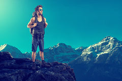 Reaching the Summit. Man reaches the top of the mountain Royalty Free Stock Photo