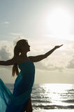 Reaching to catch the sun. A blonde woman in profile standing at the waterin a sheer dress is reaching up to catch the sun in her hand Stock Photography