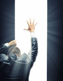 Reaching to light. Businessman opening some gate and reaching hand to a bright light royalty free stock image