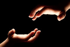 Reaching to touch. Two hands reaching in the darkness to touch Royalty Free Stock Photography