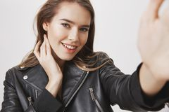 Reaching to you to express her sympathy and affection. Attractive sensual european woman touching neck and pulling hand. Towards camera, smiling broadly Royalty Free Stock Images
