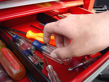 Reaching for Tools Stock Image
