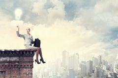 Reaching the top. Fearless businesswoman with suitcase sitting on building top Royalty Free Stock Images