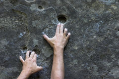 Reaching up. Hands of man climbing holding on and reaching for the next hand hold stock photography