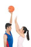 Reaching up. Sportive girl reaching to the ball held by her cheerful friend royalty free stock image
