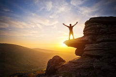 Reaching Up Into The Sky. A person expressing freedom - reaching up into the sky against a sunset stock photo