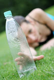 Reaching for water. A girl lying on the green grass after aerobic wanted to drink some water Stock Photo