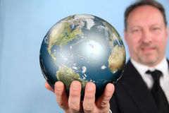 Reaching The World. Businessman Presenting the World on His Outstretched Hand Royalty Free Stock Photos