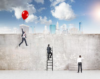 Reaching your aim. A businessman flying a red balloon, a businessman climbing a ladder and one standing at a concrete wall separating them from New York, blue stock images