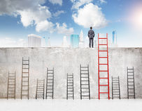 Reaching your aim. A businessman with hands in pockets standing on a concrete wall separating him from New York. Several ladders of different size at the wall stock image