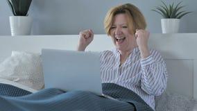 Reactie van Succes door Gelukkige Hogere Vrouw die Laptop in Bed met behulp van stock video
