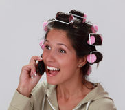 Reaction on the phone. Young woman with hair curlers talking happilly on the mobile phone Stock Photography