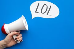 Reaction to something funny. Internet meme LOL. Megaphone near cloud with word LOL on blue background top view copy. Reaction to something funny. Internet meme stock image