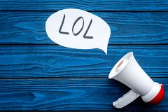 Reaction to something funny. Internet meme LOL. Megaphone near cloud with word LOL on blue wooden background top view. Reaction to something funny. Internet meme stock photo