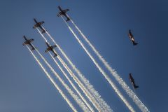 Reactive jet plane flying in formation on blue sky. Reactive jet plane flying in formation and leave inversion trail on blue sky Stock Image